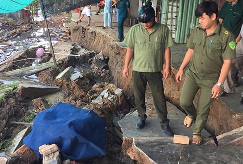 Lực lượng chức năng hỗ trợ người dân di dời tài sản ra khởi khu vực sụt lún nguy hiểm.
