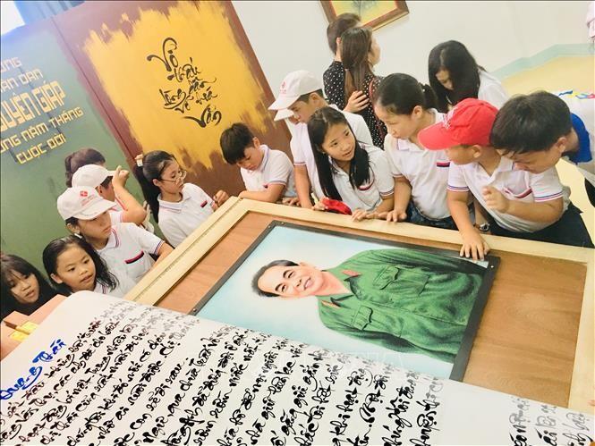 Các em học sinh hào hứng tham quan quyển sách thư pháp viết về Đại tướng Võ Nguyên Giáp.