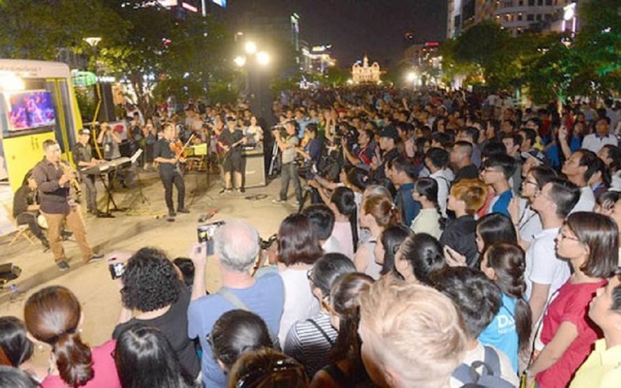 Người dân xem chương trình nghệ thuật đường phố tại phố đi bộ Nguyễn Huệ, quận 1, TPHCM.