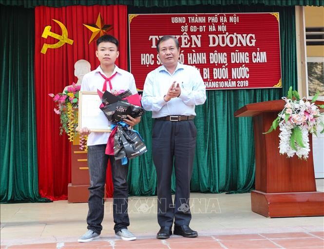 Phó Giám đốc Sở Giáo dục và Đào tạo Hà Nội Lê Ngọc Quang trao Bằng khen của Chủ tịch UBND thành phố Hà Nội cho em Phan Trung Hiếu. Ảnh: Thanh Tùng/TTXVN
