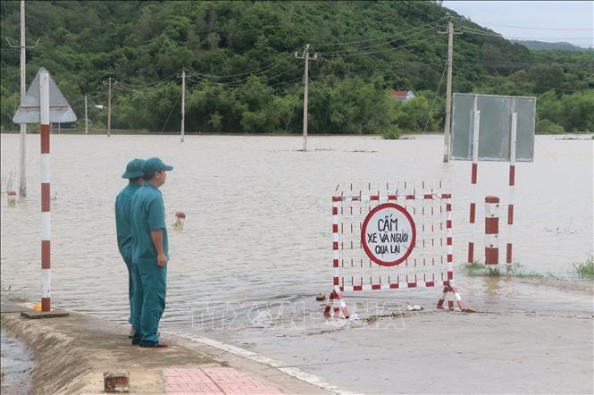 Lực lượng chức năng trực chốt tại khu vực cấm người dân qua tuyến đường DT642 thị trấn La Hai, huyện Đồng Xuân (Phú Yên) bị ngập do nước lũ. Ảnh: Phạm Cường/TTXVN