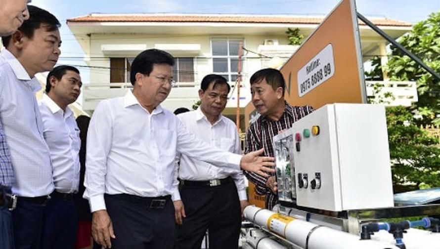 Phó Thủ tướng Trịnh Đình Dũng xem xét một thiết bị lọc nước nhiễm mặn tại Bến Tre