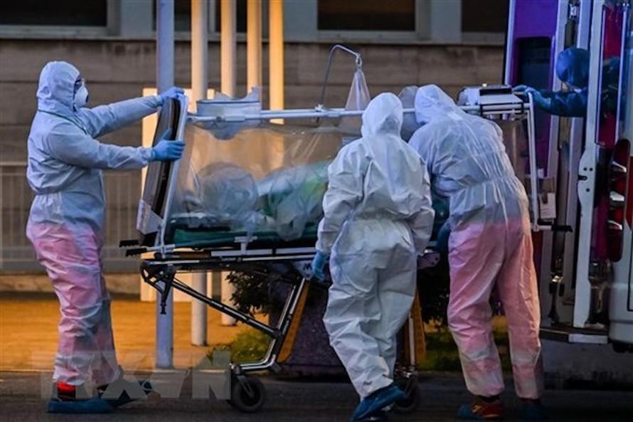Nhân viên y tế chuyển bệnh nhân mắc COVID-19 tại một bệnh viện ở Rome, Italy ngày 16/3/2020. (Ảnh: AFP/TTXVN)