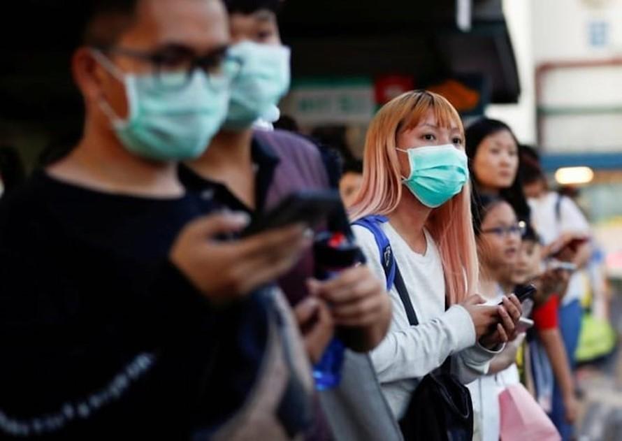 Người dân chờ đợi lên xe buýt đi từ Woodlands Causeway, bang Johor, Malaysia để tới Singapore trước khi Malaysia cấm toàn bộ các hoạt động di chuyển. Ảnh minh họa: Reuters.