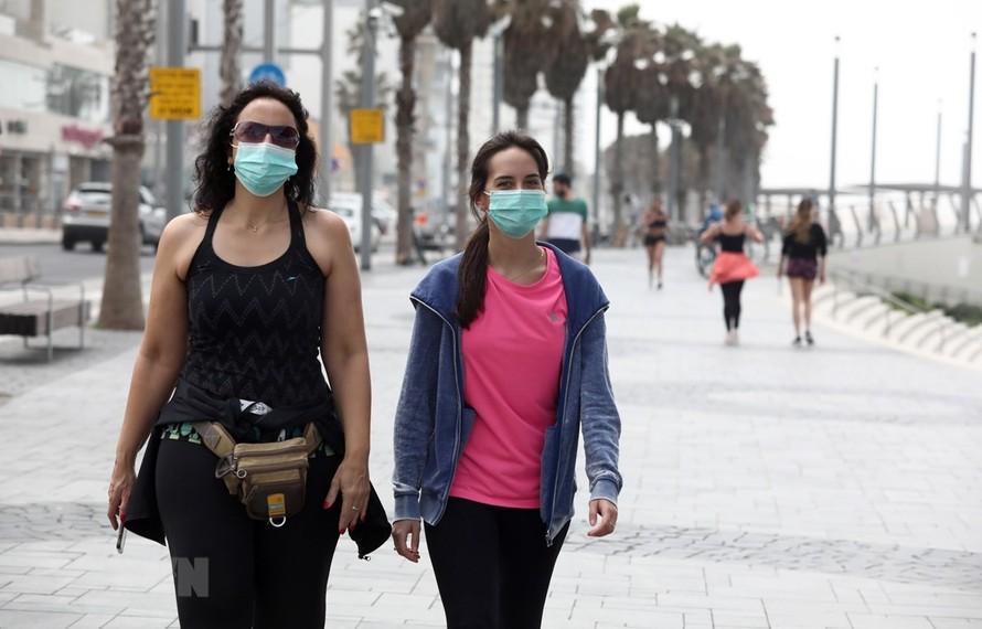 Người dân đeo khẩu trang phòng dịch COVID-19 khi di chuyển tại thành phố miền Trung Tel Aviv. (Ảnh: THX/TTXVN)