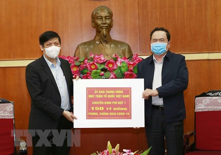 Chủ tịch Ủy ban Trung ương MTTQ Việt Nam Trần Thanh Mẫn trao tượng trưng kinh phí cho đại diện Bộ Y tế. (Ảnh: Doãn Tấn/TTXVN)