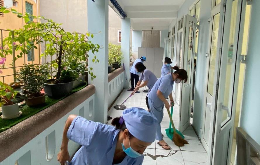 Cán bộ, giáo viên và nhân viên Trường Tiểu học Nguyễn Tri Phương (quận Ba Đình) vệ sinh trường lớp, sẵn sàng đón học sinh.