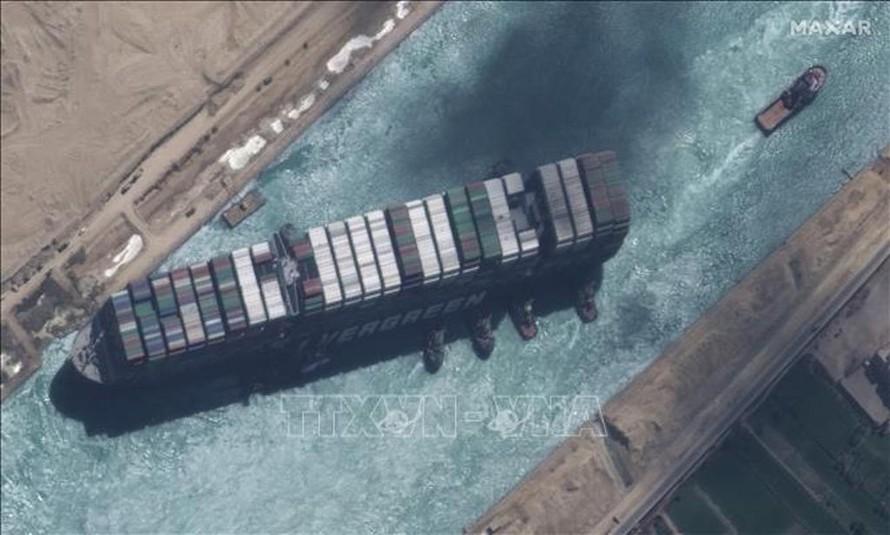Toàn cảnh siêu tàu container Ever Given (trái) bắt đầu nổi lên và được tàu kéo lai dắt sau một tuần mắc kẹt trên kênh đào Suez ở Ai Cập, ngày 29/3/2021.