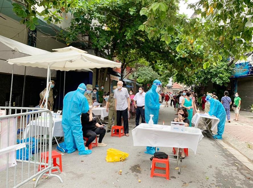 Nhân viên y tế lấy mẫu xét nghiệm cho người dân trên địa bàn quận Đống Đa, Hà Nội.