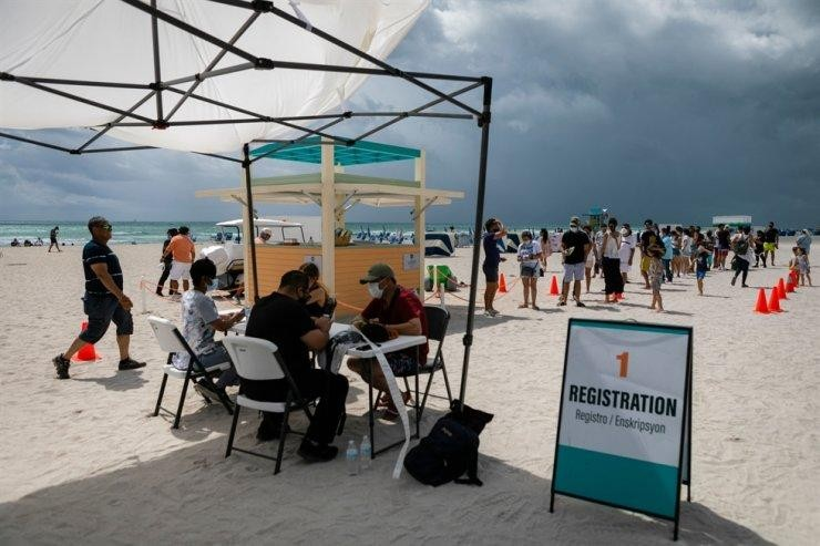 Mọi người đăng ký tiêm chủng vaccine ngừa COVID-19 tại một bãi biển ngày 9/5. (Ảnh: AFP-Yonhap)