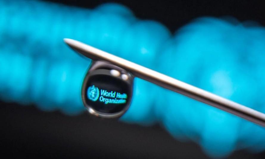 Logo của Tổ chức Y tế Thế giới được phản chiếu qua một giọt kim tiêm ngày 16/3 (Ảnh: Reuters)