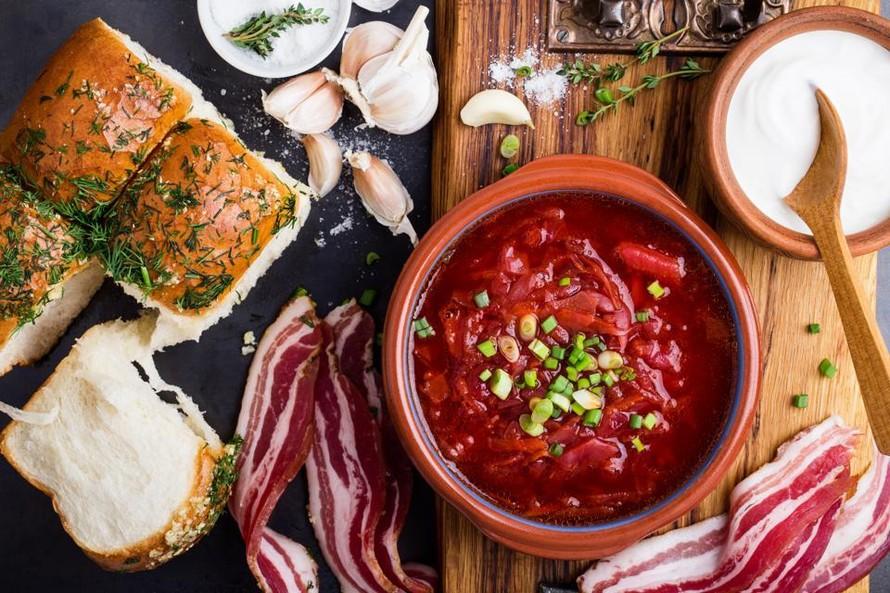 Súp củ cải đỏ borscht trong bát sứ với bánh tỏi pampushka và thịt ba chỉ khô. (Ảnh: Forbes)