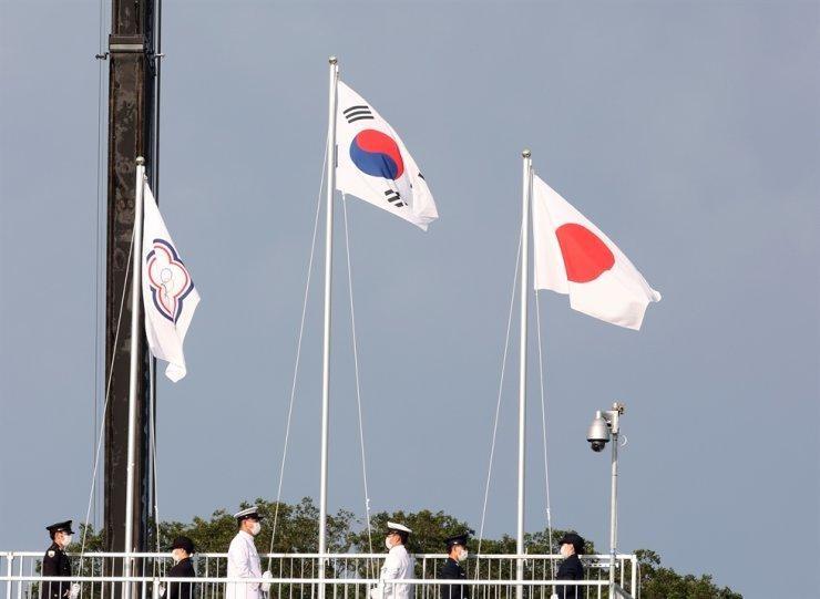Cờ của 'Đài Bắc Trung Hoa' (Đài Loan), bên trái, tại Lễ trao huy chương cho nội dung bắn cung nam ở Trường bắn cung Công viên Yumenoshima, Tokyo, hôm thứ Hai. Lá cờ có hình một mặt trời nhỏ màu trắng đặt trên một vòng tròn màu xanh lam - một biểu tượng được lấy từ quốc kỳ Đài Loan - và năm vòng tròn Olympic, được bao quanh bởi một bông hoa mận châu Á màu xanh, trên nền trắng. (Ảnh: Yonhap)