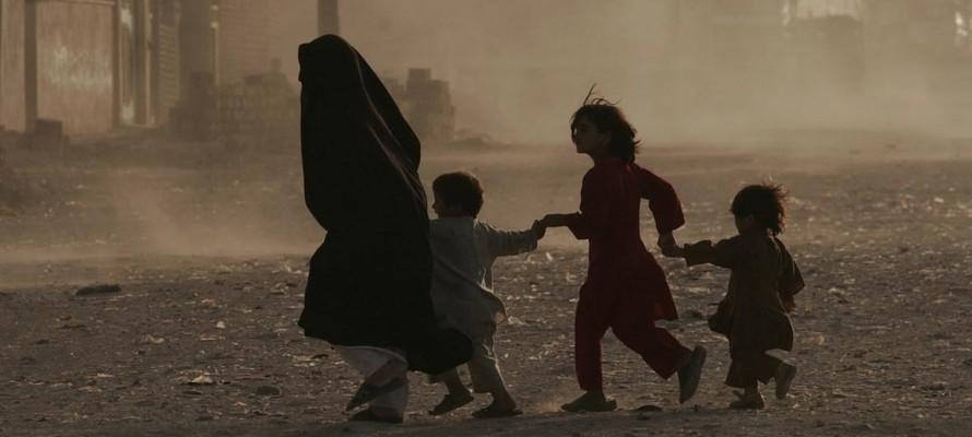 Một gia đình chạy băng qua con phố đầy bụi ở Herat, Afghanistan. (Ảnh: Fraidoon Poya)