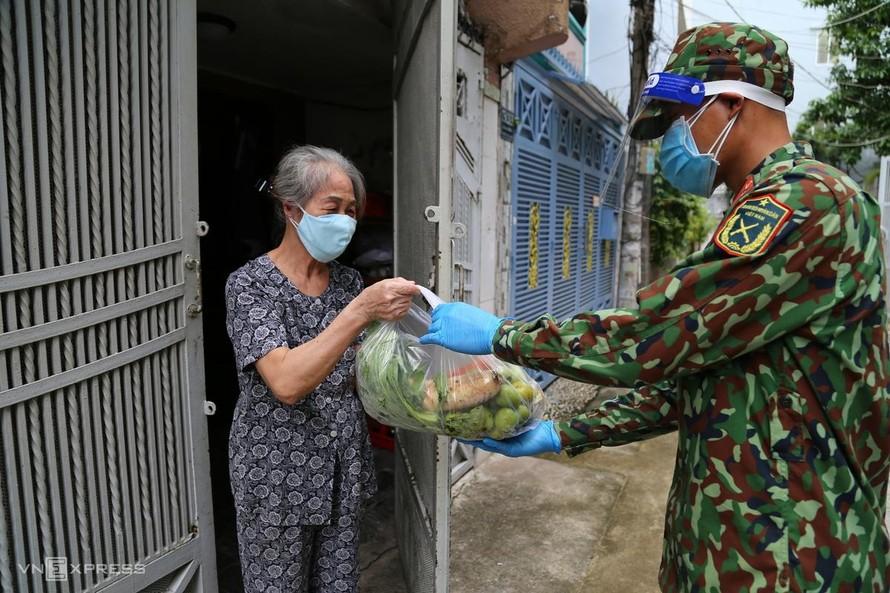 Bà Lê Thị Ánh, 73 tuổi, vui mừng khi nhận túi rau củ đặt mua hộ từ bộ đội. Ảnh: VnExpress.