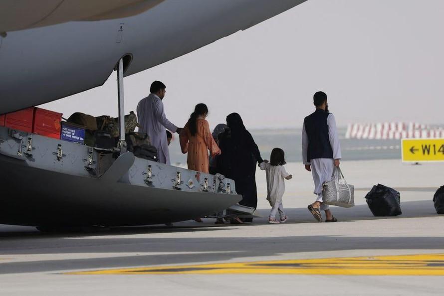 Những người sơ tán Afghanistan xuống khỏi một chiếc máy bay quân sự của Không quân Hoàng gia Anh hạ cánh tại Các Tiểu vương quốc Ả Rập Thống nhất. Sau đó, họ sẽ đi tiếp đến Vương quốc Anh. Ảnh: GIUSEPPE CACACE / AFP