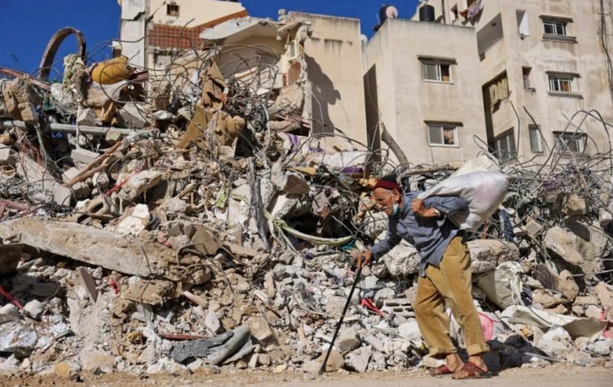 Người đàn ông Palestine đi ngang qua một tòa nhà bị phá hủy bởi cuộc bắn phá của Israel ở Gaza. Ảnh: