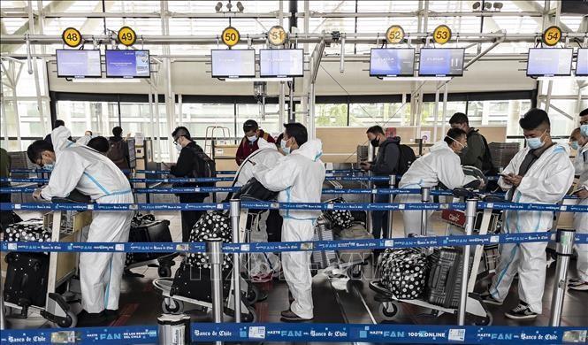 Hành khách trang bị trang phục phòng dịch COVID-19 khi chờ làm thủ tục tại sân bay quốc tế Arturo Merino Benitez ở Santiago, Chile ngày 1/4/2021. Ảnh: AFP/TTXVN