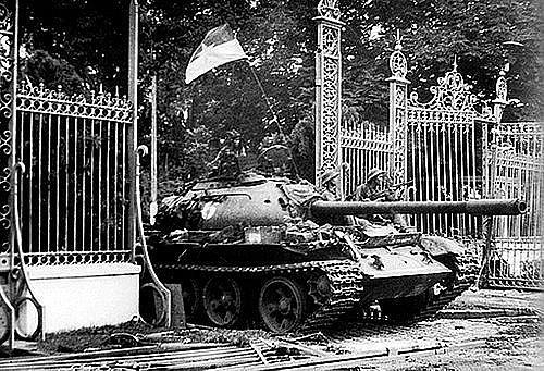 Đoàn xe tăng húc đổ cổng chính, tiến vào chiếm Dinh Độc Lập sáng 30/4. Đại đội trưởng Bùi Quang Thận ra khỏi xe 843, lấy lá cờ Tổ quốc trên xe của mình treo lên cột cờ trên nóc Dinh Độc Lập lúc 11h30 (ảnh tư liệu).