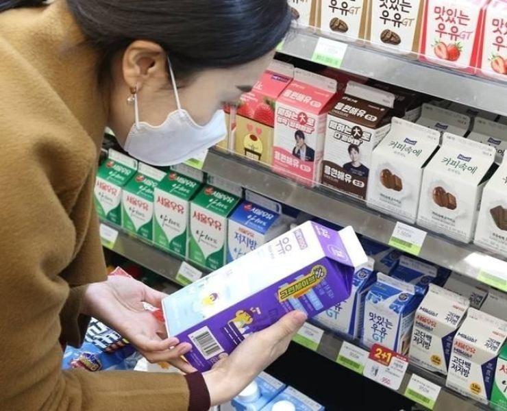 Một người tiêu dùng Hàn Quốc đang đọc hạn sử dụng in trên vỏ hộp sữa (Ảnh: The Korea Times)