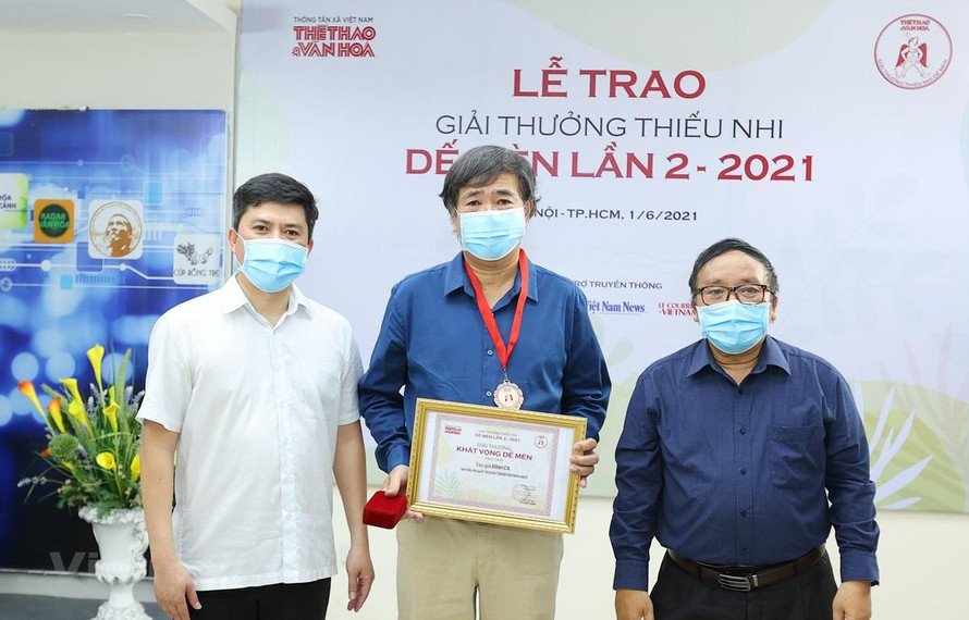 Ông Lê Xuân Thành, Trưởng Ban tổ chức Giải (trái) và nhà thơ Trần Đăng Khoa, Chủ tịch Hội đồng giám khảo (phải) trao giải cho tác giả Bình Ca (giữa). (Ảnh: Hòa Nguyễn/Vietnam+)