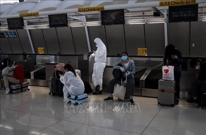 Hành khách đeo khẩu trang và mặc đồ bảo hộ phòng lây nhiễm COVID-19 tại sân bay John F. Kennedy ở Queens, New York, Mỹ. Ảnh tư liệu: AFP/TTXVN