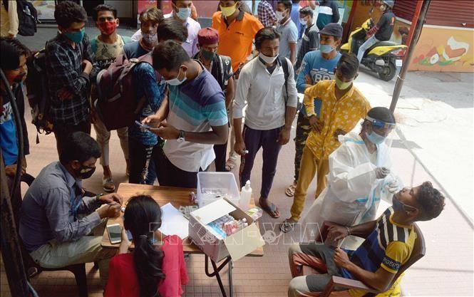 Nhân viên y tế lấy mẫu xét nghiệm COVID-19 cho người dân tại Bangalore, Ấn Độ. Ảnh: THX/TTXVN