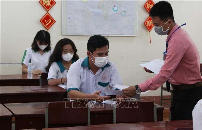 Thí sinh tại điểm thi trường THPT chuyên Vị Thanh (thành phố Vị Thanh, tỉnh Hậu Giang) nhận phiếu làm bài thi trắc nghiệm. Ảnh: Hồng Thái/TTXVN