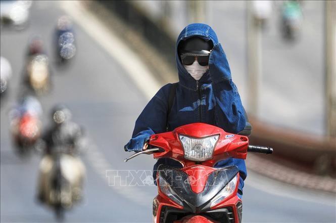Người dân trang bị khẩu trang, áo chống nắng kín mít khi tham gia giao thông. Ảnh minh họa: Thành Đạt/TTXVN
