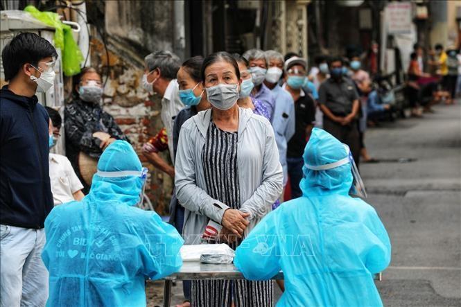 Người dân tại ngõ Trần Quý Cáp, phường Văn Chương xếp hàng đăng ký lấy mẫu xét nghiệm COVID-19. Ảnh: Thành Đạt/TTXVN
