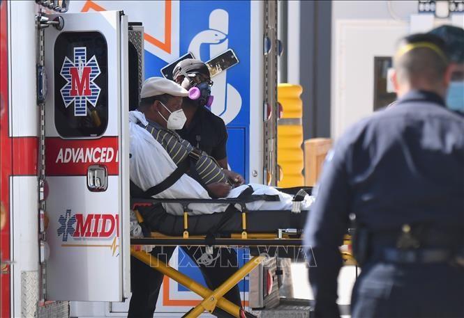 Nhân viên y tế chuyển bệnh nhân COVID-19 tới trung tâm y tế tại New York, Mỹ. Ảnh: AFP/TTXVN