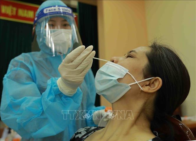 Lấy mẫu xét nghiệm sàng lọc SARS-CoV-2. Ảnh: TTXVN.