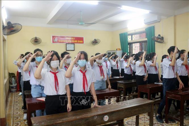 Các học sinh trường THCS Trần Phú (Phủ Lý) thực hiện nghi lễ chào cờ trong buổi khai giảng ngay tại lớp thông qua hệ thống trực tuyến của trường, ngày 5/9/2021.