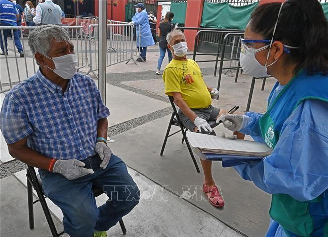 Nhân viên y tế lấy mẫu xét nghiệm COVID-19 cho người dân tại Lima, Peru. Ảnh tư liệu: AFP/TTXVN