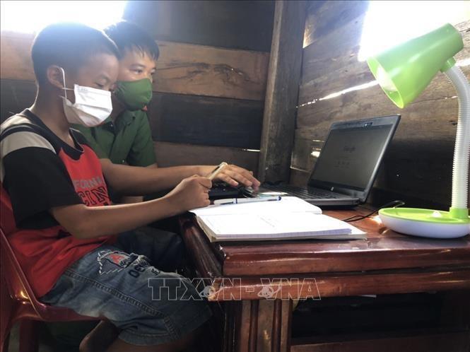 Thiếu tá Lê Anh Tuấn, Đội tổng hợp Công an huyện Cư M'Gar hướng dẫn học sinh có hoàn cảnh khó khăn sử dụng laptop do anh trao tặng. Ảnh minh họa: TTXVN phát.