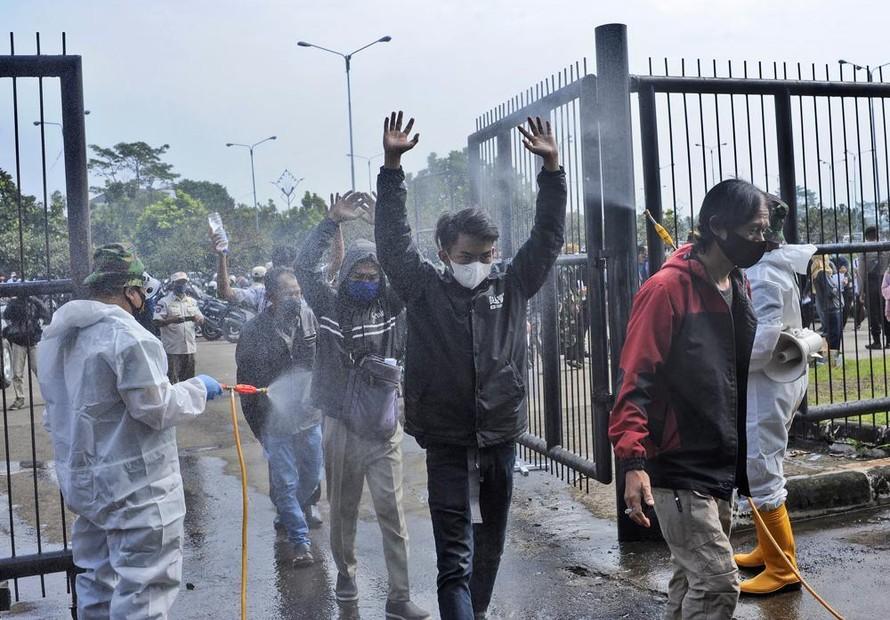 Binh sĩ Indonesia xịt khử trùng lên người dân đến sân vận động tại Tây Java để tiêm vaccine COVID-19. Ảnh: AP