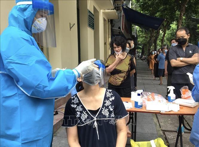 Lấy mẫu xét nghiệm cho người dân sàng lọc ca nhiễm SARS-CoV-2. Ảnh: TTXVN